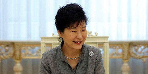 FILE PHOTO: South Korean President Park Geun-hye smiles as she listen to a reporter's question during...