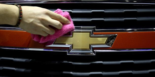 An event staff member wipes a General Motors Corp. (GM) Chevrolet Trax vehicle during the press day of...