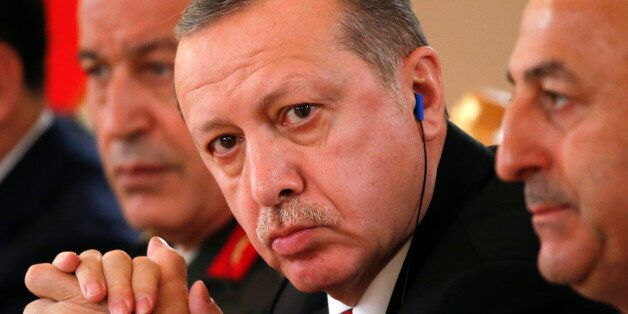 Turkish President Tayyip Erdogan (C) attends a meeting with his Russian counterpart Vladimir Putin at...