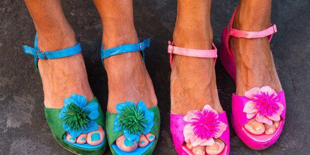 Four pretty pedicured feet in flowery sandals,