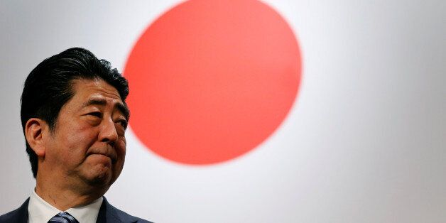 Japan's Prime Minister Shinzo Abe stands in front of Japan's national flag after his ruling Liberal Democratic...