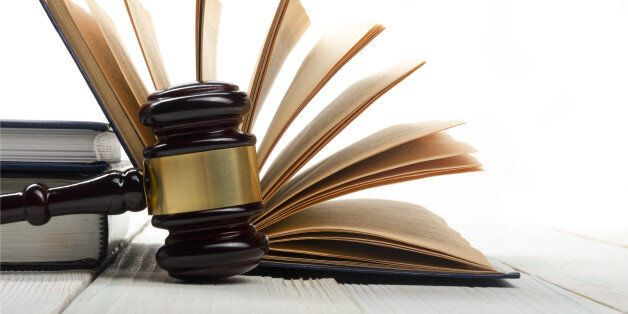 Law concept - Open law book with a wooden judges gavel on table in a courtroom or law enforcement office...