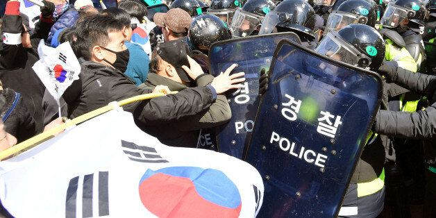 Protesters supporting South Korean President Park Geun-hye clash with riot policemen near the Constitutional...