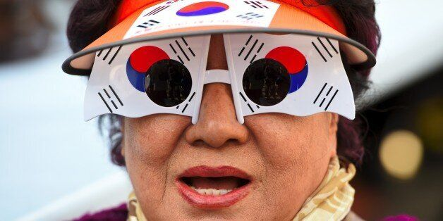 A supporter of South Korea's impeached-President Park Geun-Hye wears glasses painting the national flag...