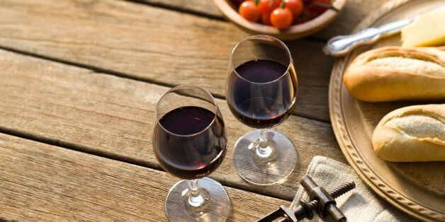 Red wine on a rustic picnic table.More rustic outdoor wine