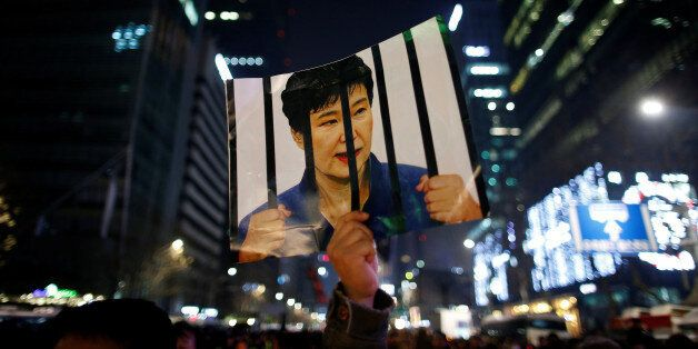 A man holds up a picture bearing an image of South Korean President Park Geun-hye as he attends a ceremony...