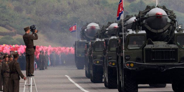 A North Korean soldier films military vehicles carrying missiles during a parade to commemorate the 65th...