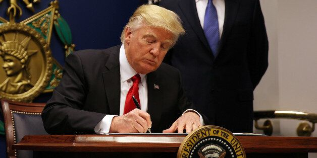 U.S. President Donald Trump signs a revised executive order for a U.S. travel ban on Monday, leaving...