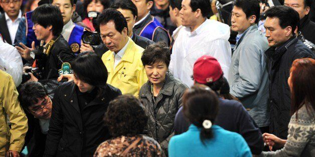 South Korea's President Park Geun-Hye (C) visits relatives of missing passengers on board a capsized...