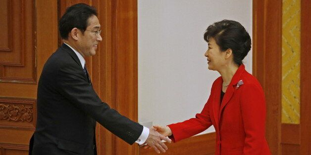 South Korea President Park Geun-hye (R) shakes hands with Japanese Foreign Minister Fumio Kishida during...