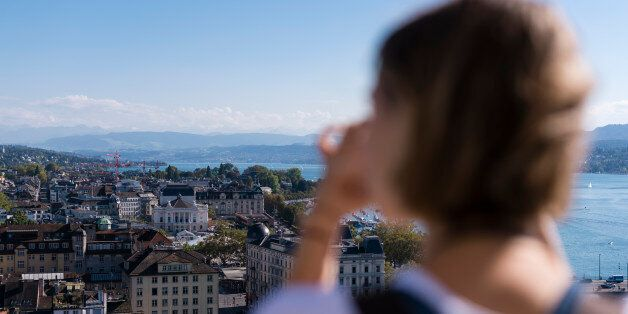 Zurich, Switzerland - 30 September 2016: A female tourist is taking pictures of Zurich from the observation...