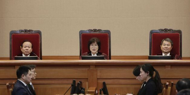South Korean acting Constitutional Court's Chief Judge Lee Jung-mi, center, attends the final hearing...