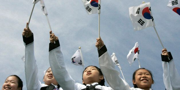 Girls wave national flags during the 90th anniversary of the Independence Movement at Independence Hall...