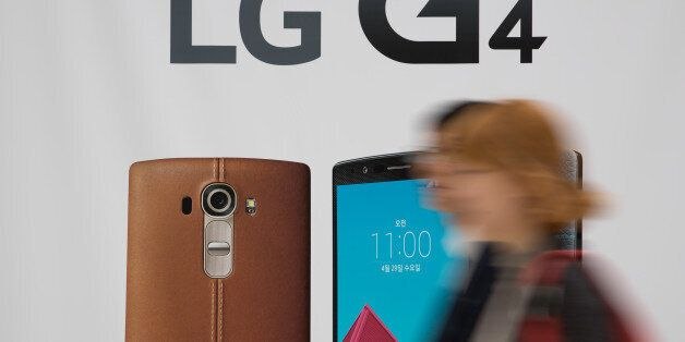 People walk past an advertisement for LG Electronics Inc.'s G4 smartphone at a promotional booth in the...