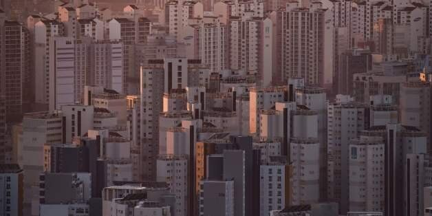 A general view shows apartment buildings and the city skyline at sunrise in Seoul on December 10, 2016.A...