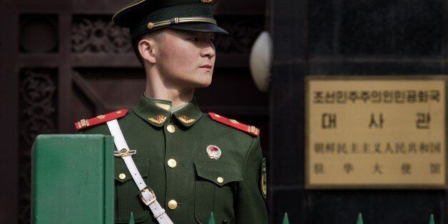 A paramilitary police officer stands guard in front of the North Korean embassy in Beijing on March 6,...