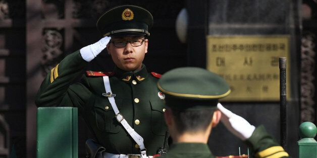 Chinese paramilitary police officers salute each other at the entrance of the North Korean embassy in...