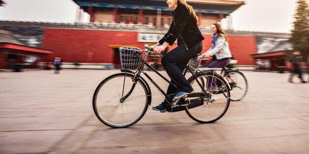 Friends riding retro bicycles along forbidden
