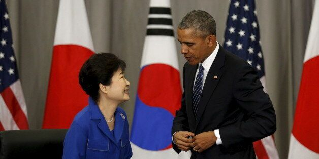 U.S. President Barack Obama speaks with South Korean President Park Geun-Hye after their trilateral meeting...