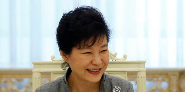 South Korean President Park Geun-hye smiles as she listen to a reporter's question during an interview...