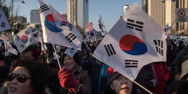 Pro-government activists shout slogans and wave flags as they stage a rally in central Seoul on February...