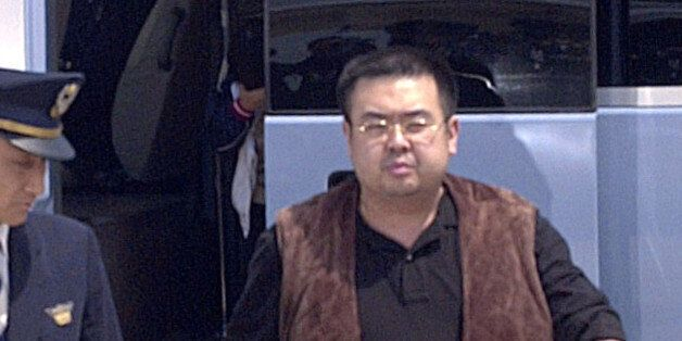 A man (R) believed to be North Korean heir-apparent Kim Jong Nam, is escorted by police as he boards...