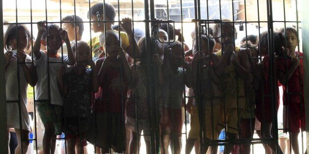 Children wait at the gates for free meals during a feeding program given by volunteers from a religious...