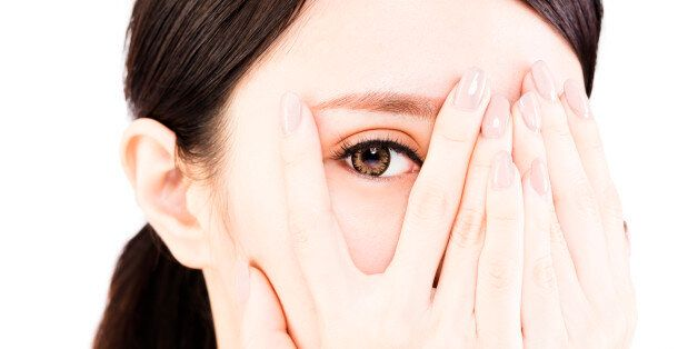 young woman covering her eyes by