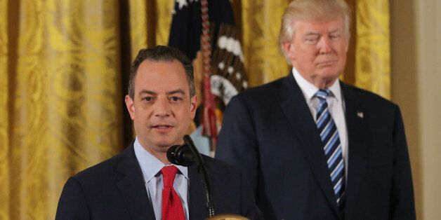 U.S. President Donald Trump stands behinds Chief of Staff Reince Priebus after a swearing-in ceremony...
