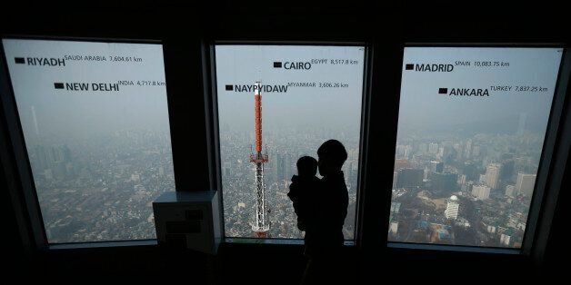 A man holds his baby while viewing central Seoul shrouded in heavy haze at an observation platform