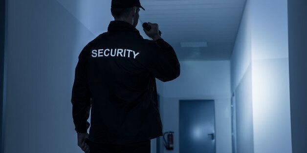 Rear view of security guard with flashlight in building