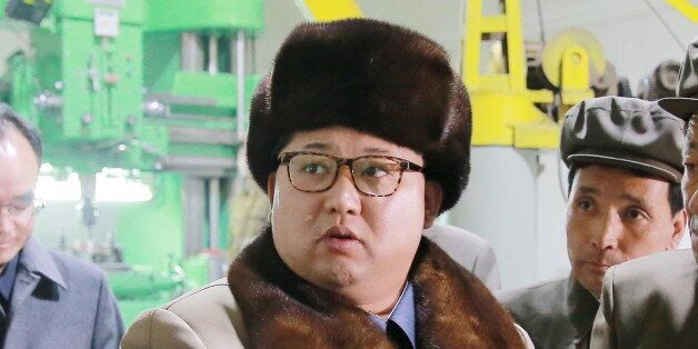 North Korean leader Kim Jong Un (C) speaks during a visit to the Sinhung Machine Plant in this undated...