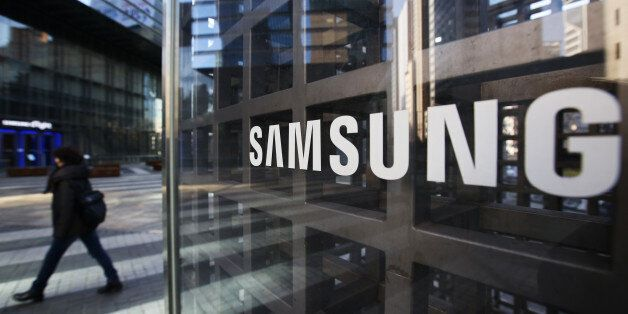 A woman walks past Samsung Electronics Co. signage outside the company's Seocho office building in Seoul,...