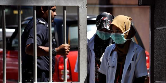 A Malaysian police personnel mans the main gate as medical staff leave the Forensic wing at the Hospital...