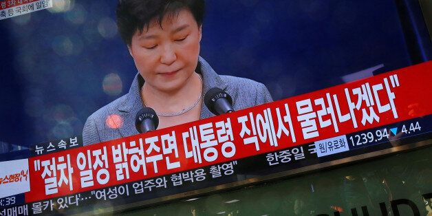 People watch a television broadcast of a news report on President Park Geun-hye releasing a statement...