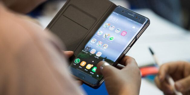 A woman checks her Samsung Electronics Co. Galaxy Note 7 smartphone at a Samsung kiosk providing rental...