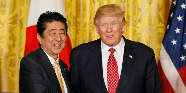 Japanese Prime Minister Shinzo Abe (L) and U.S. President Donald Trump shake hands following their joint...