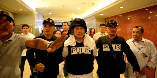 Police officer Ricky Sta. Isabel (C), one of the suspects in the kidnapping and murder of South Korean...