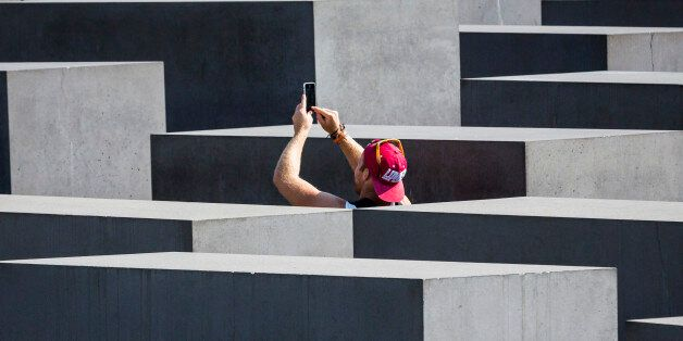 BERLIN, GERMANY - SEPTEMBER 04: Tourists taking a photo of the concrete slabs, stelae of the Memorial...