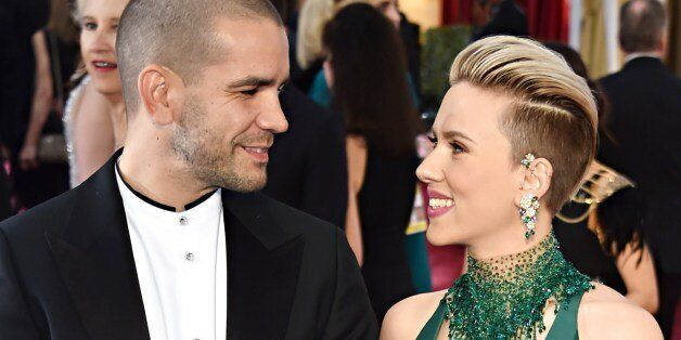 Scarlett Johansson (R) and Romain Dauriac pose on the red carpet for the 87th Oscars on February 22,...