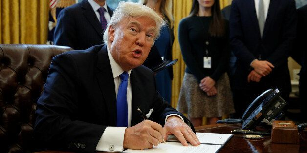 U.S. President Donald Trump looks up while signing an executive order to advance construction of the...