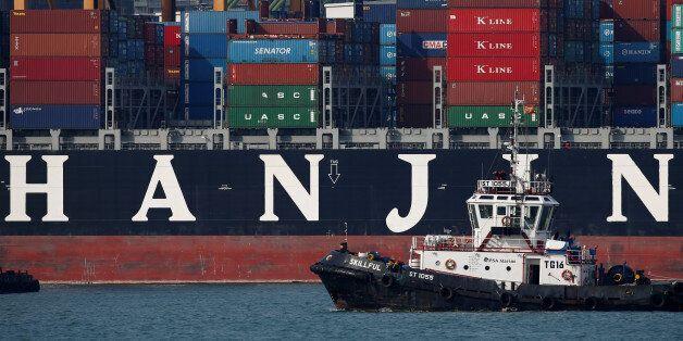 A tugboat passes Hanjin Hungary container ship at PSA's Tanjong Pagar terminal in Singapore September...
