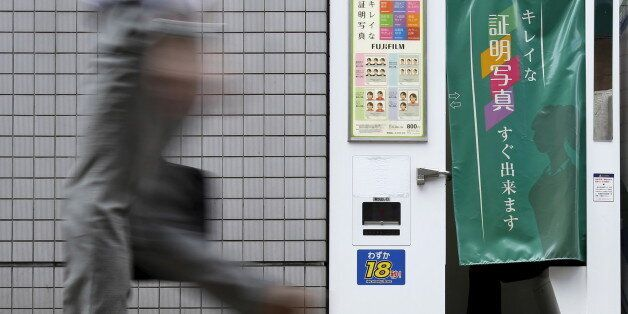 A pedestrian walks past an ID photo machine box as a man sits inside at a business district in Tokyo,...
