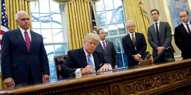 US President Donald Trump signs an executive order in the Oval Office of the White House in Washington,...