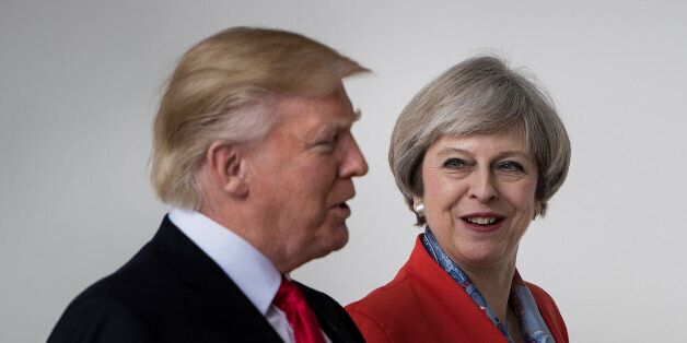 US President Donald Trump and British Prime Minister Theresa May walk at the White House on January 27,...