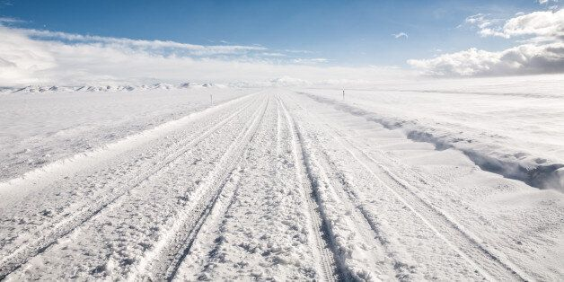 A snow covered road leads through an empty winter landscape under clear sky. Near Garrison,
