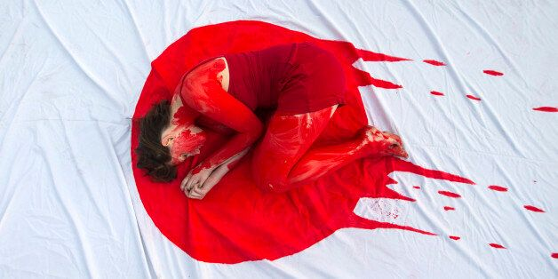 An Israeli member of the 'Taiji Dolphin Action Group', with a red body painting to evok blood, is curled...