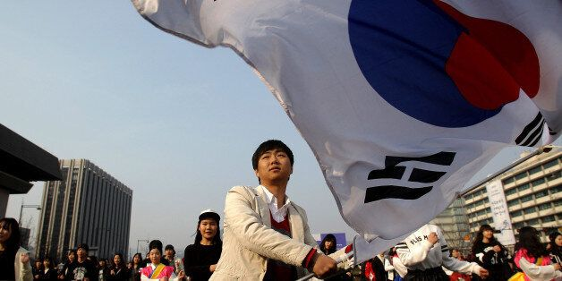 SEOUL, SOUTH KOREA - FEBRUARY 22: A South Korean student waves national flags during an anti-Japan rally...
