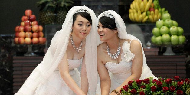You Ya-ting (L) and Huang Mei-yu cast their stamps during their symbolic same-sex Buddhist wedding ceremony...