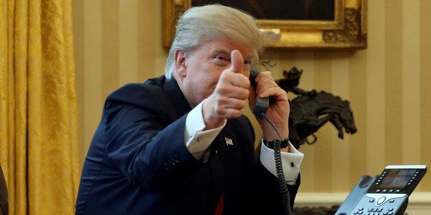 U.S. President Donald Trump gives a thumbs-up to reporters as he waits to speak by phone with the Saudi...